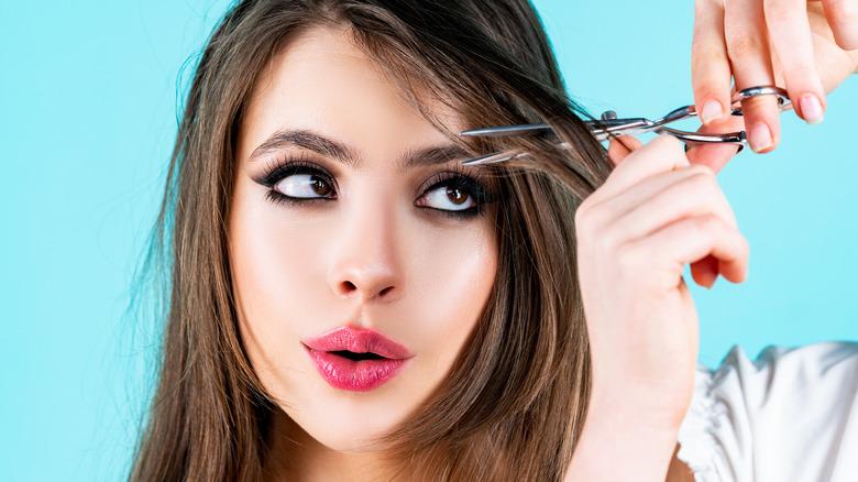 woman cutting hair bangs
