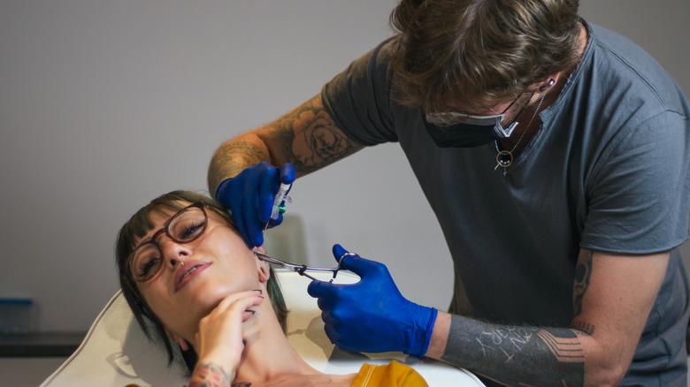 Woman getting a piercing