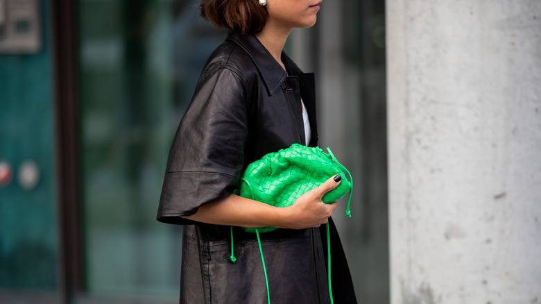 Desirée Kastull with kelly green bag, white dress, and brown coat at Copenhagen Fashion Week