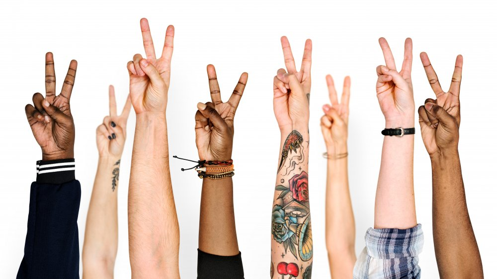 many hands making peace signs