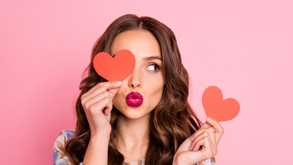 brunette with a pout and heart cutouts in hand