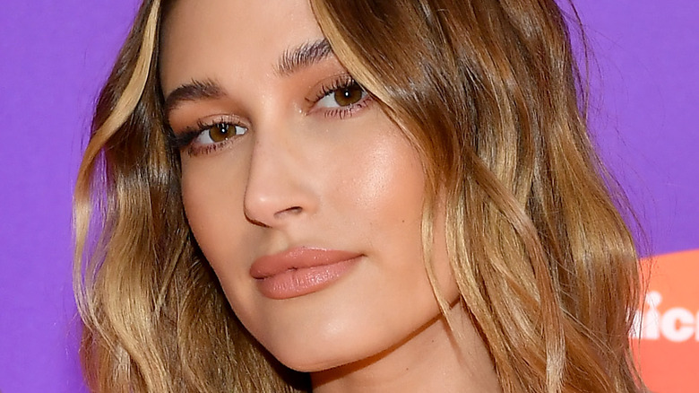Hailey Bieber smiles with wavy ombre hair.