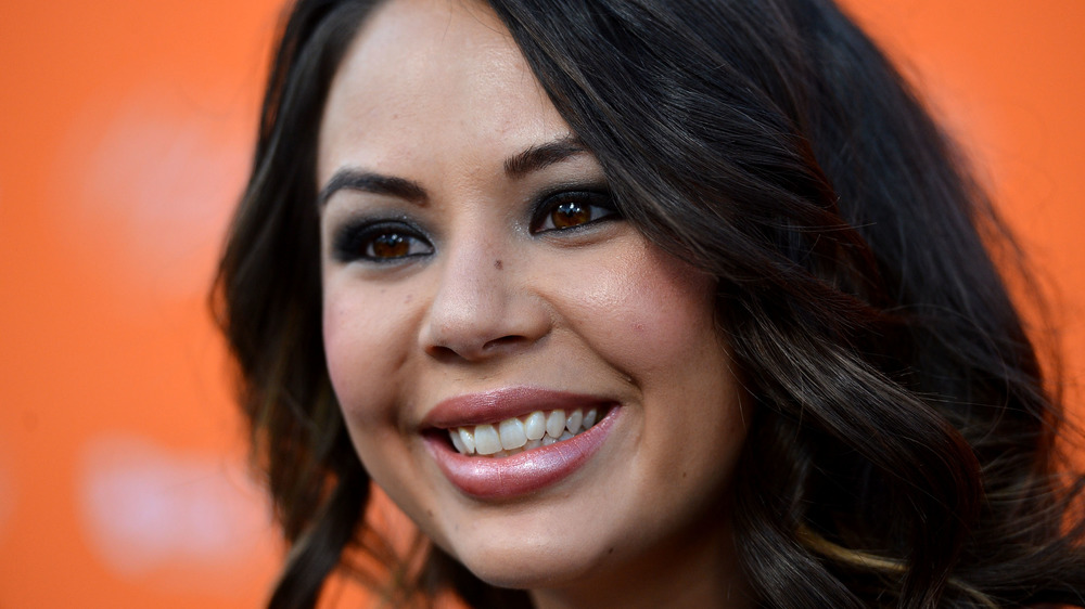 Janel Parrish smiling on the red carpet