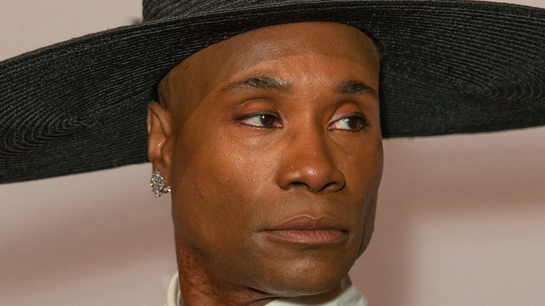 Billy Porter poses with pink eyeshadow and a black hat