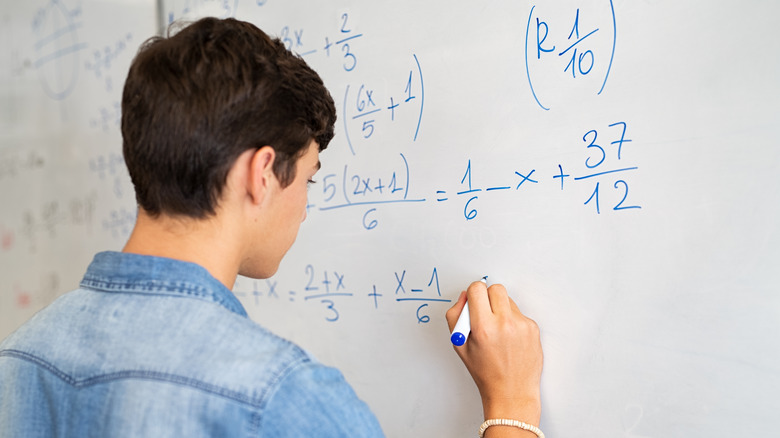 Person solving math equations on a whiteboard
