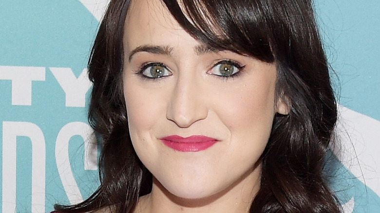 Mara Wilson smiles and poses at an event
