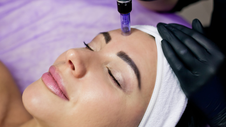 Woman smiling while getting her facial