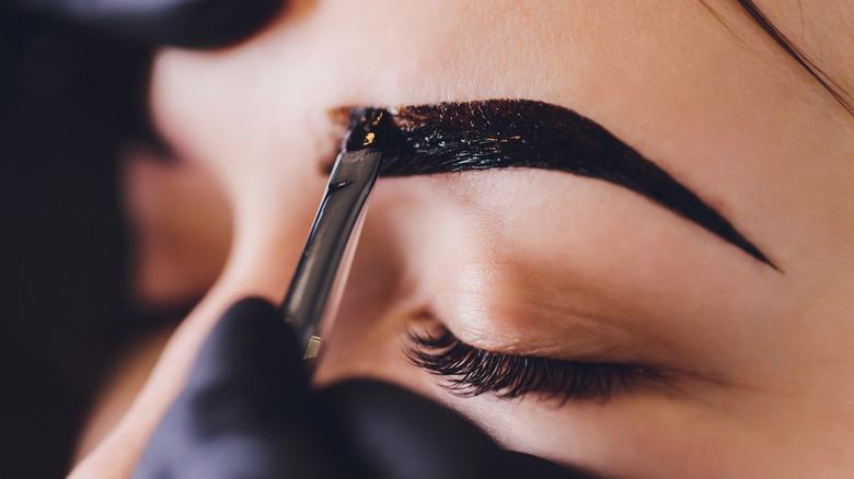 Woman getting henna eyebrows