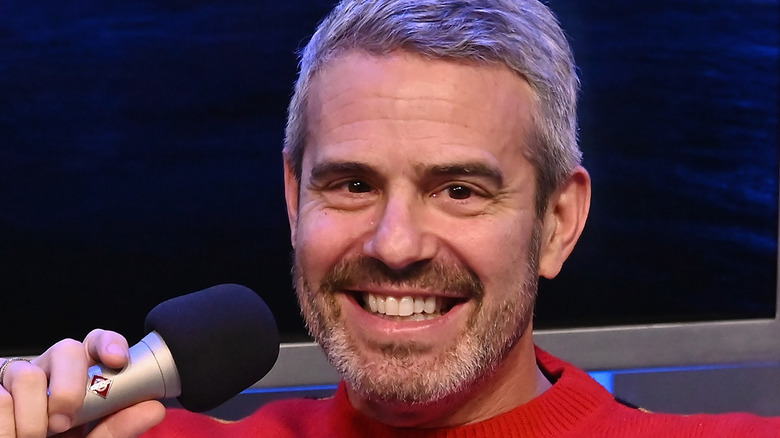 Andy Cohen holding microphone