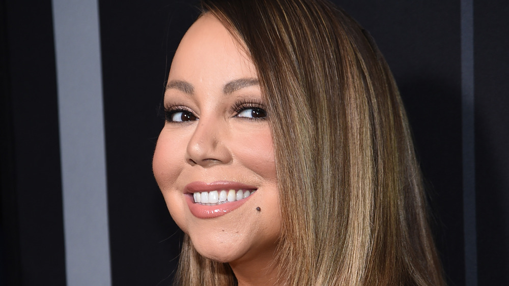 Mariah Carey smiles with straight hair