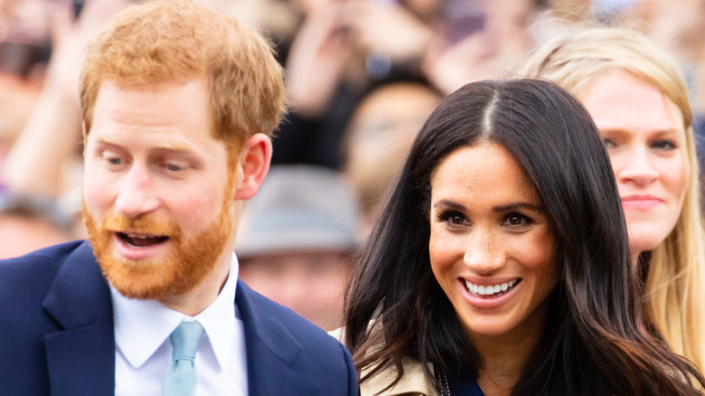 Prince Harry and Meghan Markle smiling at event