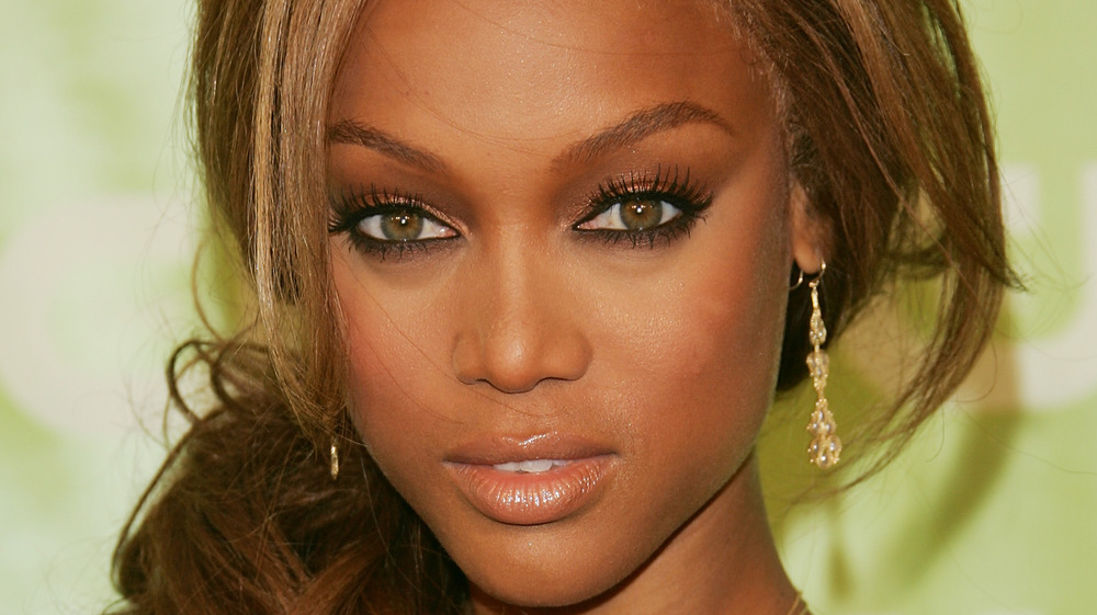 Close up of Tyra Banks in gold tones makeup against a green background
