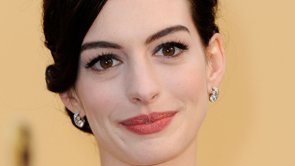 Anne Hathaway grinning with hair up
