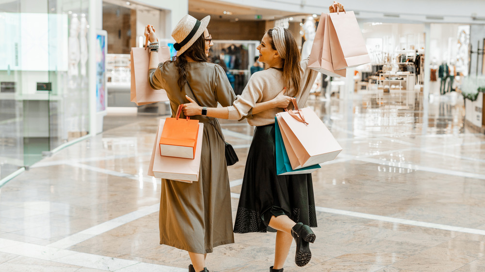 Two friends carrying shopping bags