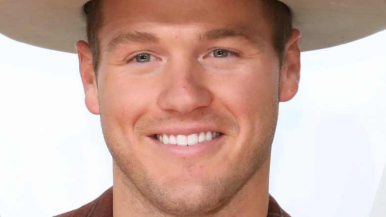 Colton Underwood smiling in hat