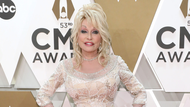 Dolly Parton smiling in off-white sequin gown
