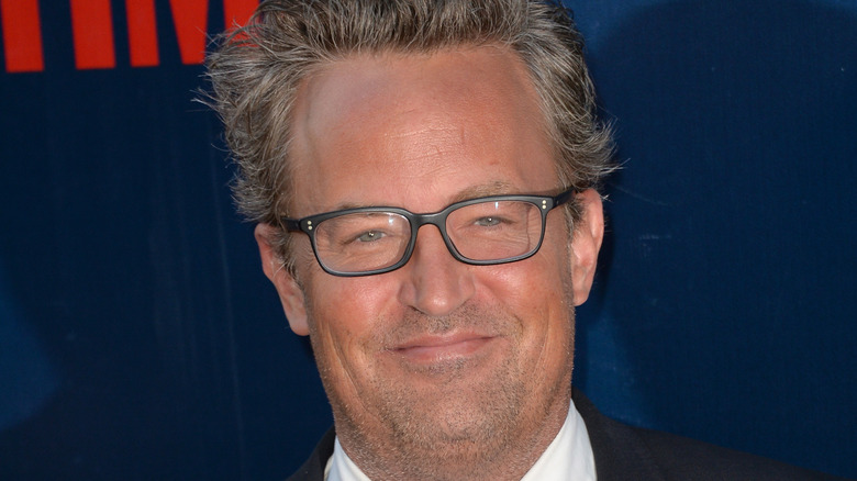 Matthew Perry smiles with glasses.