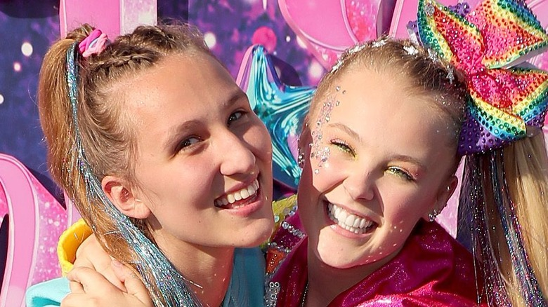 Kylie Prew and Jojo Siwa pose hugging each other and smiling