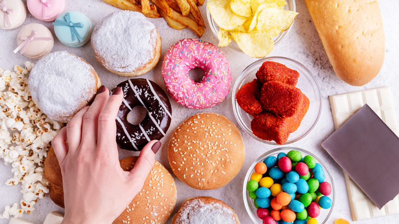 Person's hand reaching for junk food