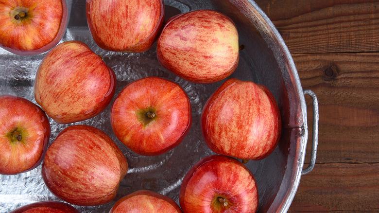 bucket of apples in water