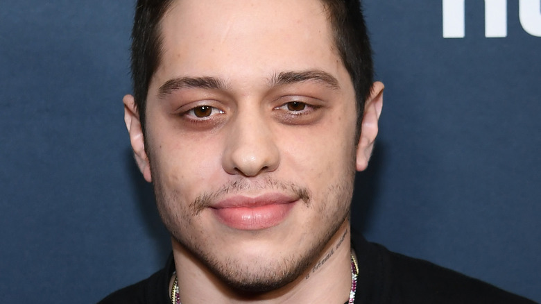 Pete Davidson grinning with facial scruff