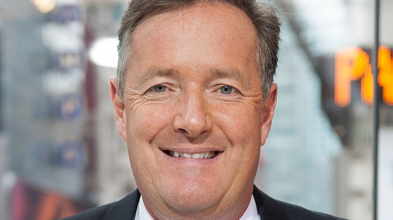 Piers Morgan smiles at an event.
