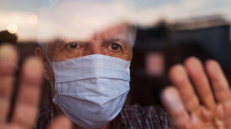 older man wearing face mask inside