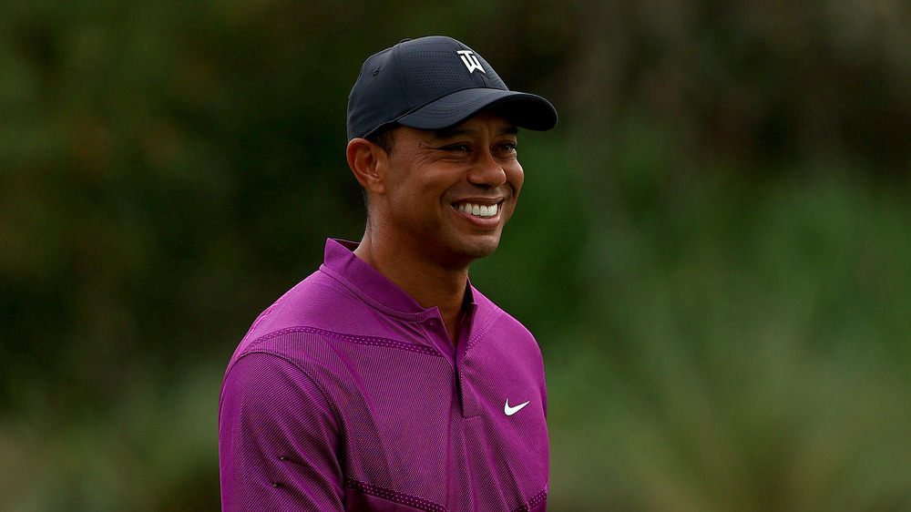 Tiger Woods smiling on the golf course