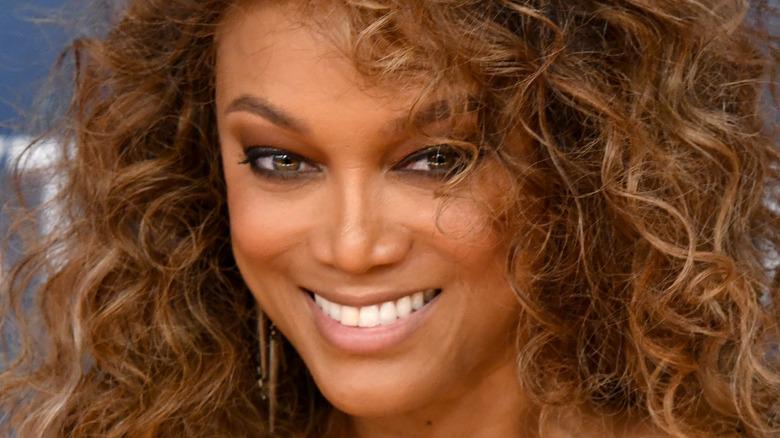 Tyra Banks smiles big with large curls.