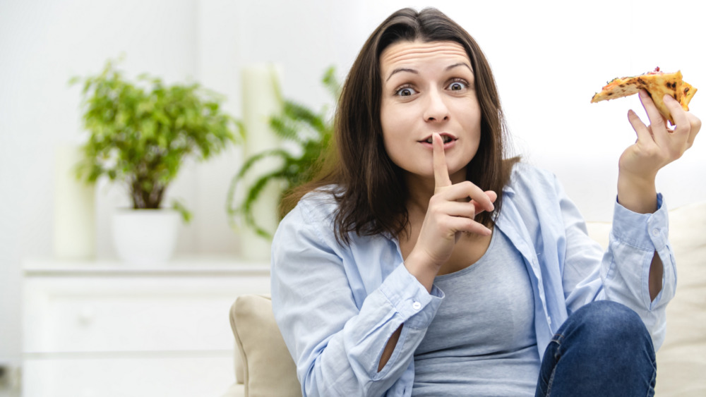 Woman sneaking slice of pizza