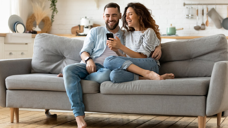 Happy couple looking at a smartphone on the couch.