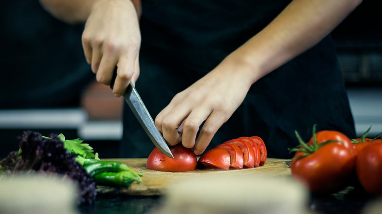 A person chops fresh vegetables with a kitchen knife