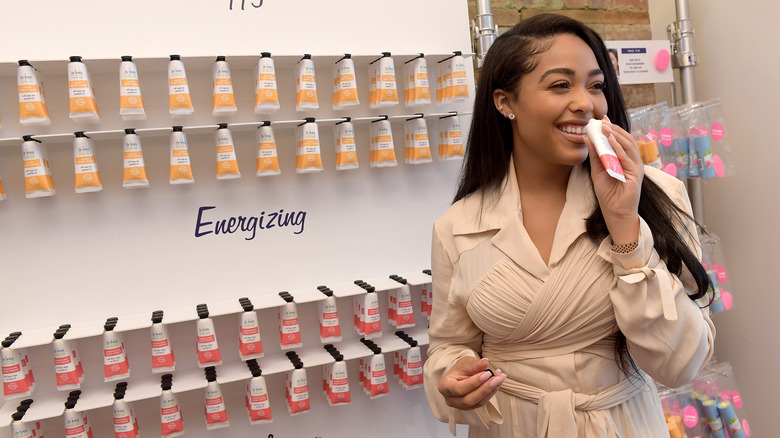 A woman poses in front of St. Ives products
