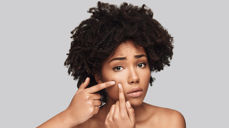 Woman with dark curly hair and bare shoulders with worried look on her face squeezes her cheek with both pointer fingers