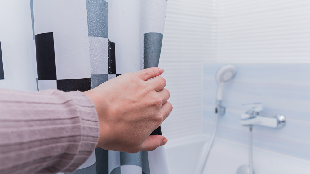 Hand pulling back shower curtain
