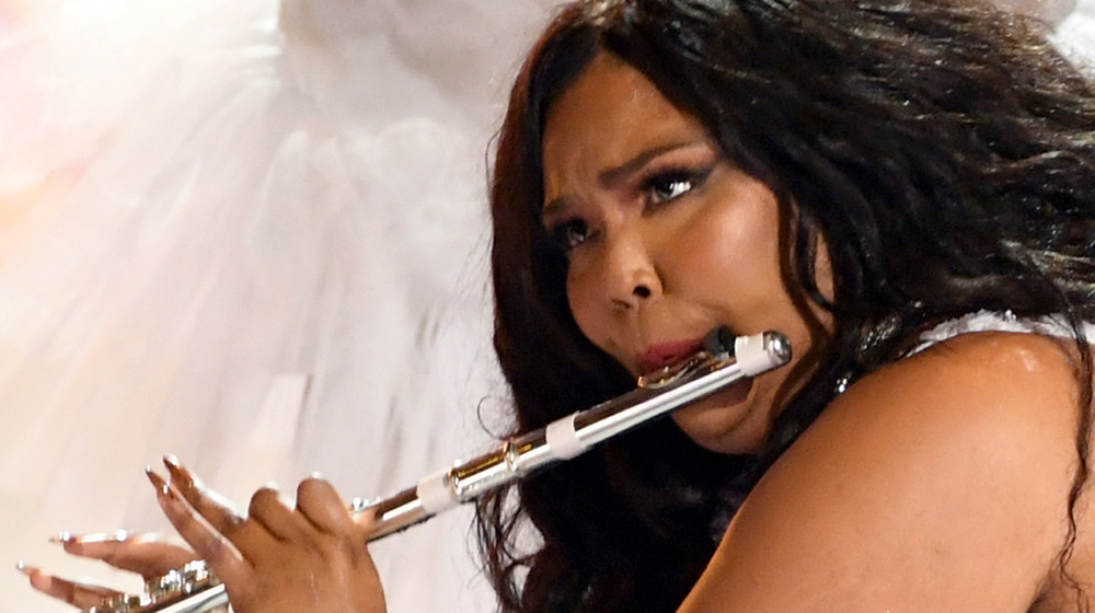 Lizzo performing onstage with her flute
