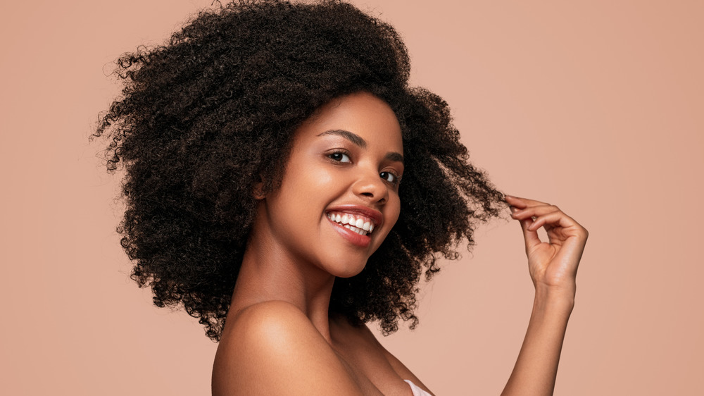 Woman touching hair and smiling.