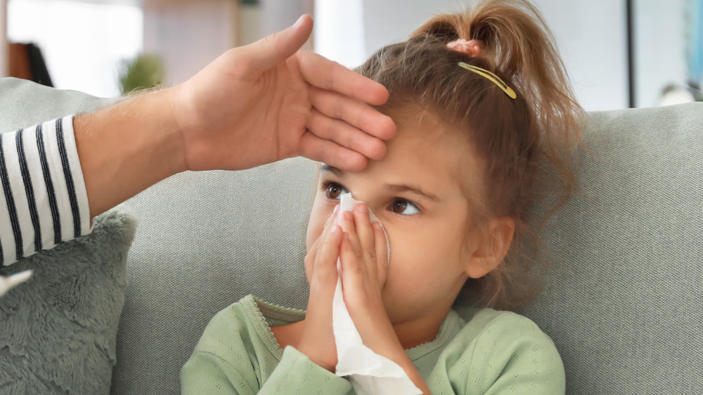Father taking care of his daughter at home with the flu
