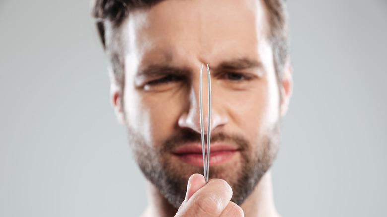 Man holding tweezers
