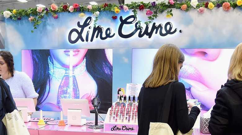 Lime Crime booth with customers checking out their products.