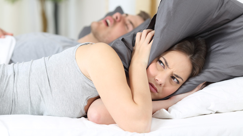 Woman annoyed by snoring