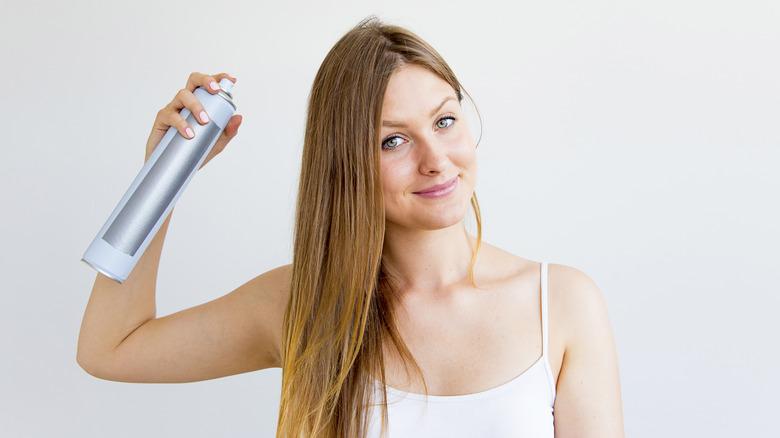 Woman spraying dry shampoo