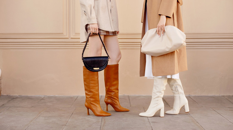 Two women holding hand bags in fashionable outfits