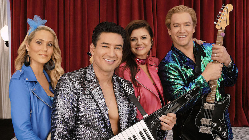 Elizabeth Berkley as Jessica Spano, Mario Lopez as A.C. Slater, Tiffani Thiessen as Kelly Kapowski, and Mark-Pal Gosselaar as Zach Morris in a promotional photo for the reboot of Saved By The Bell
