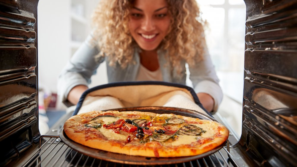 Woman taking a cooked pizza out of a home oven