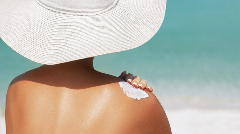 A woman in a large white hat applies sunscreen on a beach.