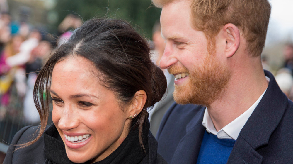 Prince Harry and Meghan Markle smiling while greeting fans