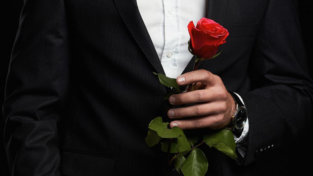 Man in tuxedo holding rose