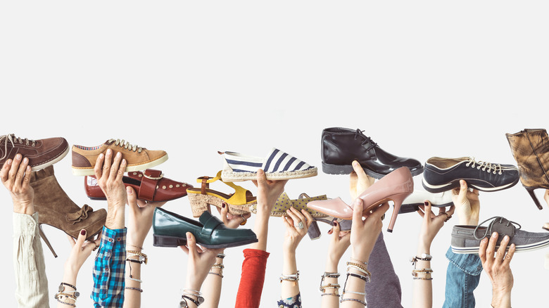 Many hands holding up different types of shoes