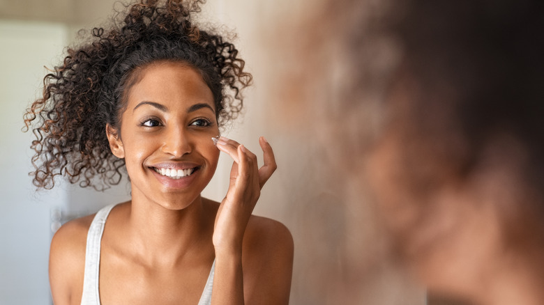 Woman smiling, putting lotion on her face